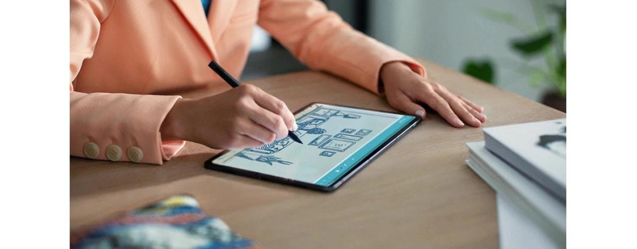 """""""Lenovo Tab P11 Pro"""" guli ant stalo su žmogumi, naudodamas planšetinį kompiuterį, pasirinkdamas """"Lenovo Precision Pen"""" rašiklį"""